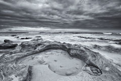 Black and white landscape of ocean rocks and clouds artistic con Royalty Free Stock Image
