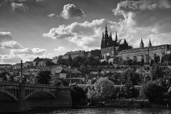 Black-and-white landscape of Prague. The prospect of a European city. Bridge, buildings and the castle on the horizon. Heavy clouds Royalty Free Stock Image