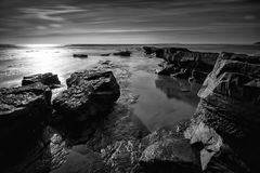 Black and white landscape of rocky shore. Stunning black and white seascape coastline and rocky shore at sunset Stock Photo
