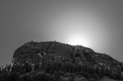 Black and White Landscape with Sun Silhouetting Mountain Royalty Free Stock Photos