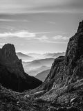 Black and white landscape view of hazy rolling mountains and hills in the Italian Dolomites at sunrise. Portrait orientation. stock photos