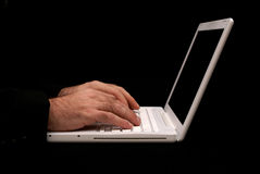 Black with white laptop. Man sitting at desk typing on the keyboard of a white laptop with black background Stock Photo