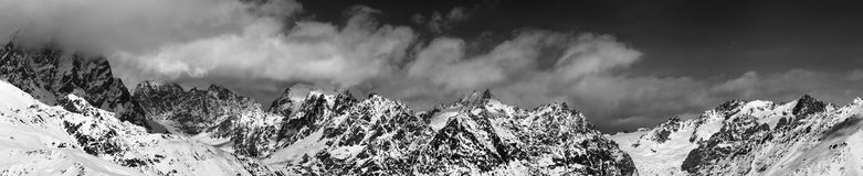 Black and white large panoramic view on snow mountains in haze a. T sunny day. Caucasus Mountains. Svaneti region of Georgia Royalty Free Stock Photo