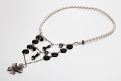 Black and white leather necklace with a silver flower Stock Images