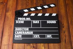Black with white letters clapper against dark wood. Black clapper-numbering with white letters for shooting a film frame on a wooden table royalty free stock photo