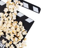 Black with white letters clapper movie and popcorn isolated on w. Black with white letters cinema-rattle and scattered popcorn isolated on white background stock image