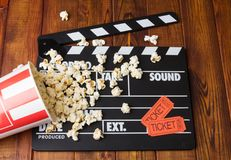 Black with white letters party poppers, box spilled popcorn and. Black with white letters party poppers, a box of spilled popcorn and movie tickets on a Royalty Free Stock Photo