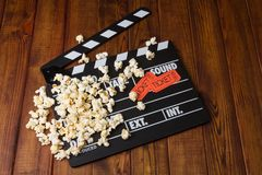 Black with white letters party poppers, popcorn and movie ticket. S on a background of dark wood Stock Photos