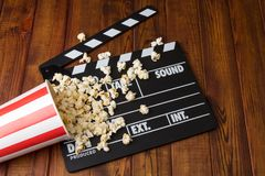 Black with white letters poppers, box of popcorn spilled on dark. Black with white letters poppers, box of popcorn spilled on a background of dark wood royalty free stock photo
