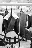 Black and white life jacket. Hang on metal rack for safety when in the boat stock photos