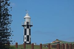 Tall black and white lighthouse at Port Shepstone, Kwazulu Natal. Black and white lighthouse against blue sky at Port Shepstone, Kwazulu Natal Royalty Free Stock Photography