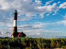 Black and White Lighthouse Near Red House Royalty Free Stock Photo