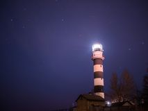 Black and white lighthouse at night in Baltic sea beach Royalty Free Stock Image
