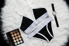 Black and white linen set for sports on a white fur. Watches, eyeshadow. Fashionable concept Stock Photo