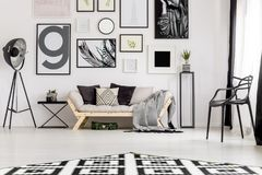 Black and white living room. Black lamp next to a settee in minimal living room interior with armchair and posters on white wall Royalty Free Stock Photo