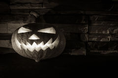 Black and white luminous halloween Jack O' lantern in dark on stone background Royalty Free Stock Image