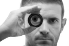 Black and white male face with magnifying lens. Male face with magnified eye whilst looking through magnifying lens with shallow DOF in black and white stock photos