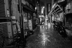 Black and white of a man with an umbrella walking down a lonely alleyway on a rainy night in Tokyo Stock Image