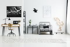 Black and white map posters. Hanging above wooden desk with laptop and metal frame bed Stock Photo