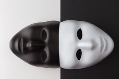Black and white masks anonymity concept. Black and white masks joined on contrasting background. Anonymity concept royalty free stock photo