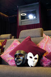 Black and white masks on couch with cushions and projector Stock Photos