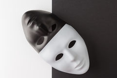 Black and white masks diagonally placed. Black and white masks placed diagonally on contrasting background. Web anonymity concept royalty free stock image