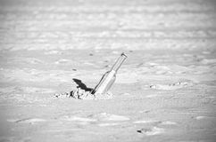 Black and white message in a bottle on sand, shallow depth of fi Royalty Free Stock Image