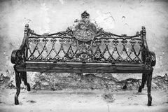 Black and white metal bench in México. Classic metal bench on the streets of México against the wall stock photo