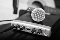 Black and white microphone on home recording studio with guitar. On background. Small soft focus put only to microphone head. Blured Stock Images