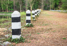 Black and white milestones on a country road. Black and white mileposts on a country road Stock Photo