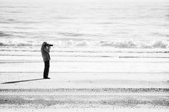 Black and white minimalist photo of senior woman photographer shooting on a Florida beach. Black & White minimalist photo of senior woman shooting on beach Stock Photo