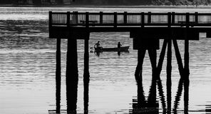 Black and white minimalist scene of a harbor with a canoe under a pier. In the water stock photos