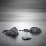 Black & White minimalist seascape with rocks. Royalty Free Stock Image