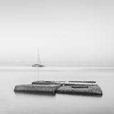 Black & White minimalist seascape with ship and rocks. Stock Images