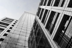 Black and white modern buildings made of steel and glass. Black and white dramatic concept of building made of steel and glass over dark sky with clouds Royalty Free Stock Image