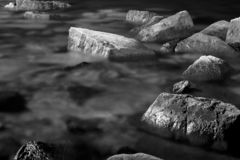 Abstract, dark, organic background, scattered rocks immersed in sea water . Black and white, monochrome, abstract, background, minimalistic composition of stock images