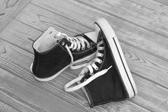 Black and white monochrome Grunge wooden background with red and white used vintage canvas sneakers Stock Images