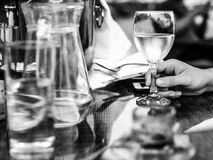Black and White Monochrome Image of a Man Holding a Glass of Whi Royalty Free Stock Photo