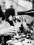 Black and White Monochrome Image of Pouring White Wine Into a Wi Royalty Free Stock Images