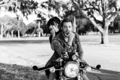 Portrait of Attractive Good Looking Young Modern Trendy Fashionable Guy Girl Couple Riding on Green Motorcycle Cruiser Old School. Black and White Monochrome royalty free stock photo