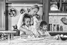 Black and white. mother`s day. mother, cooking, dough, preparation, baking, children at home, kitchen. having fun stock image