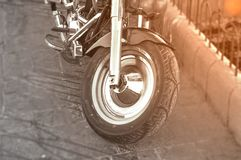 Black and white motor bike first wheel parked on city street Royalty Free Stock Photo