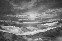 Black and white mountain italian alps landscape. Sun light behind clouds mountain valley covered with clouds in early morning just the summits of the tallest royalty free stock photography