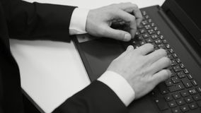 Black and white movie of male caucasian businessman sitting at desk typing on laptop computer. Close up of hands and fingers stock footage