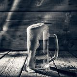 Black and white. Mug of light beer pills with foam on a wooden table in a pub stock photography