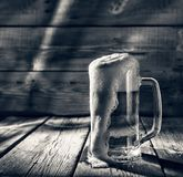 Black and white. Mug of light beer pills with foam on a wooden table in a pub royalty free stock photography