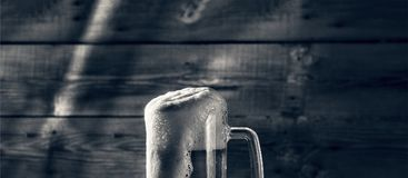 Black and white. Mug of light beer pills with foam on a wooden table in a pub stock image