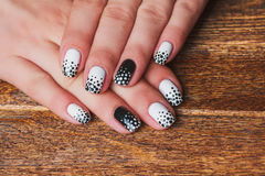 Black and white  nail art. On dark wooden background Royalty Free Stock Photo