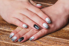 Black and white  nail art. On dark wooden background Royalty Free Stock Photography