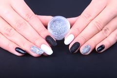 Black, white Nail art manicure. Holiday style bright Manicure with sparkles. Bottle of Nail Polish. Beauty hands. Stylish Nails, Nail Polish Royalty Free Stock Images